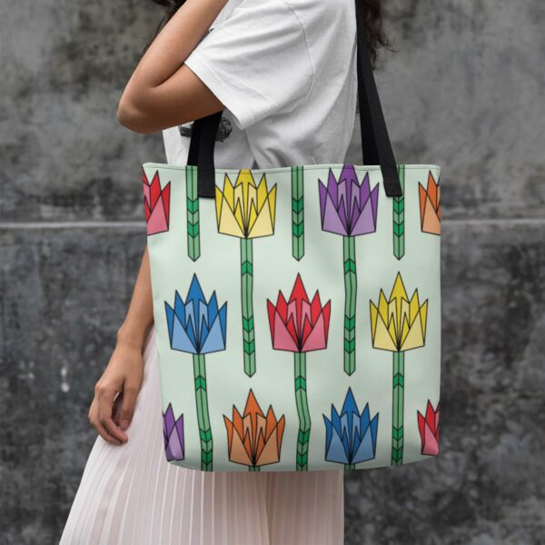 woman holding a light green tote bag with black handles and a pattern of tulip flowers in rainbow colors