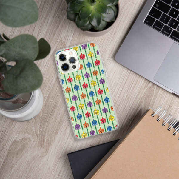 iphone case with a pattern of tulips in a midcentury style with rainbow colors sitting next to a laptop