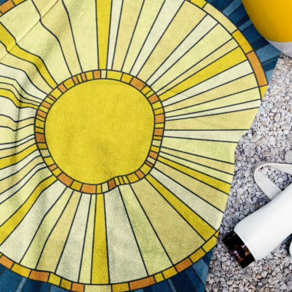 beach towel with a yellow sun design on a blue background next to a water bottle