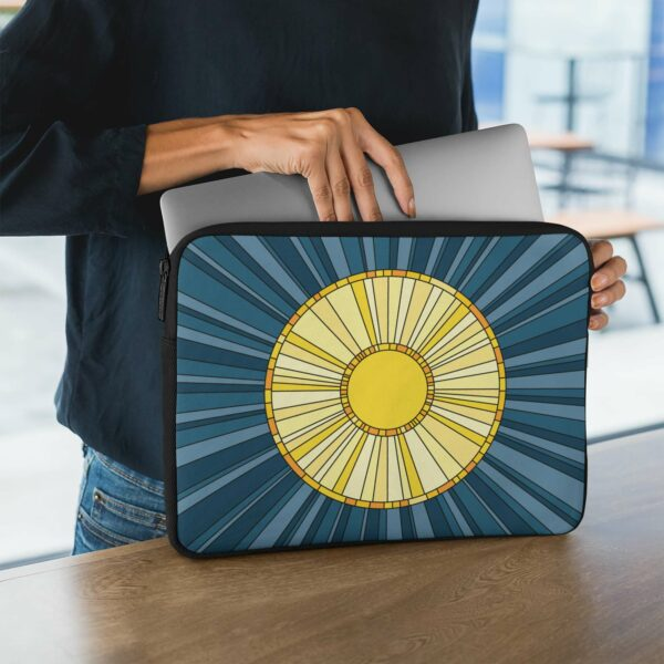 person holding a laptop sleeve with a big yellow sun on a blue background