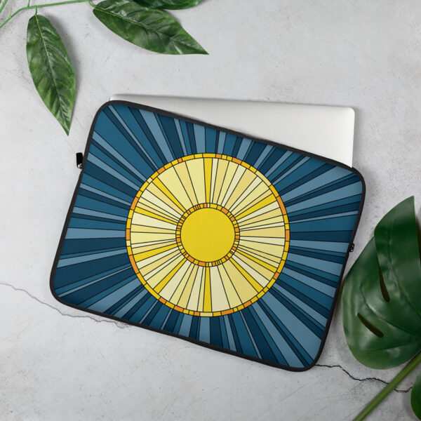 laptop sleeve with a big yellow sun on a blue background sitting on a table
