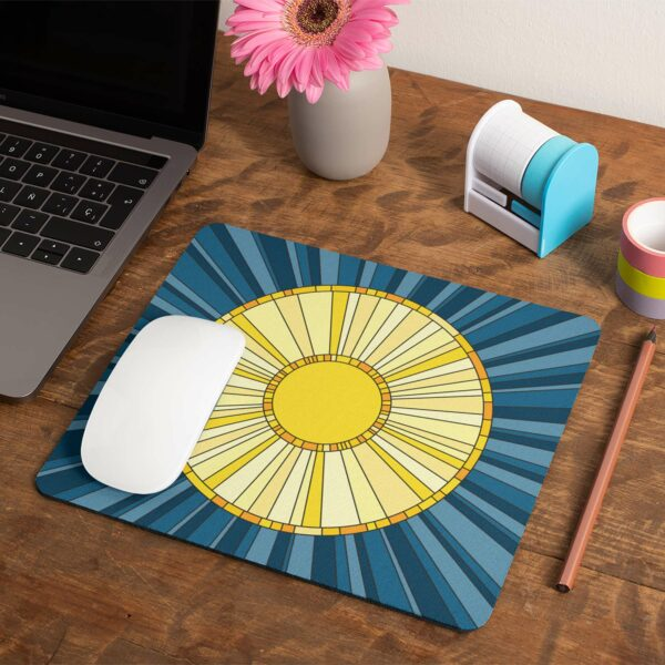 mouse pad with a yellow sun on a blue background next to a laptop
