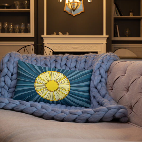 rectangle pillow with a yellow sun design on a blue background sitting on a sofa