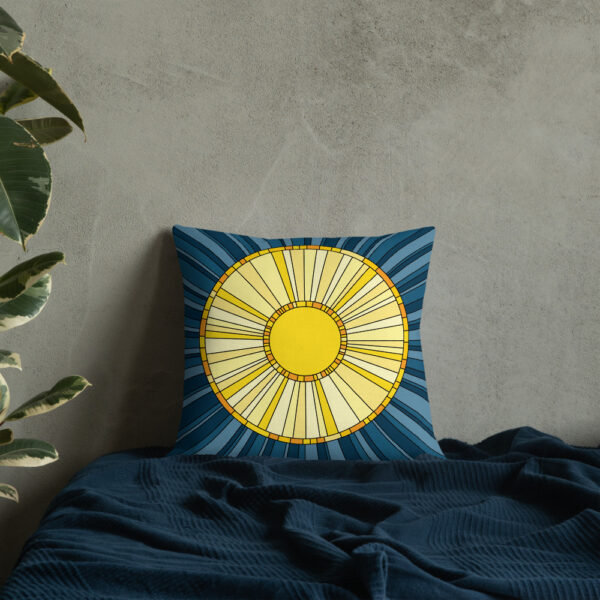 square pillow with a yellow sun design on a blue background sitting on a bed