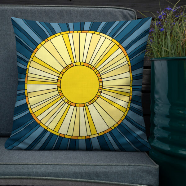 square pillow with a yellow sun design on a blue background sitting on a chair next to a plant