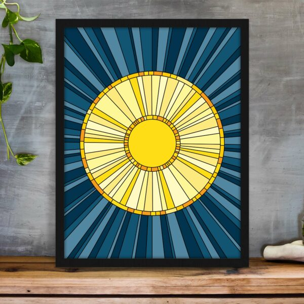 vertical fine art print with a yellow sun design on a blue background in a black frame on a table