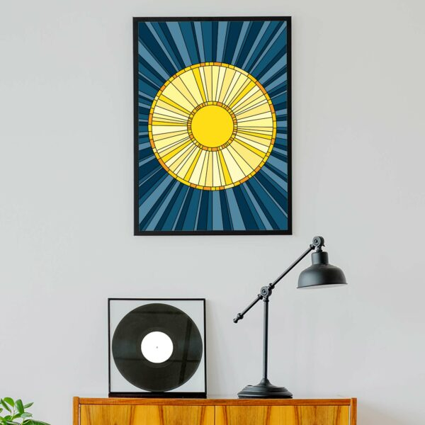 vertical fine art print with a yellow sun design on a blue background in a black frame hanging on a wall