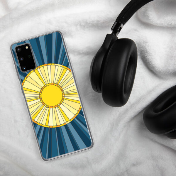 samsung phone case with a geometric design of a yellow sun on a blue background sitting next to headphones