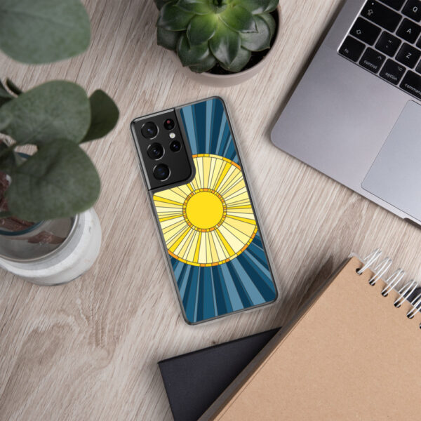 samsung phone case with a geometric design of a yellow sun on a blue background sitting next to a laptop
