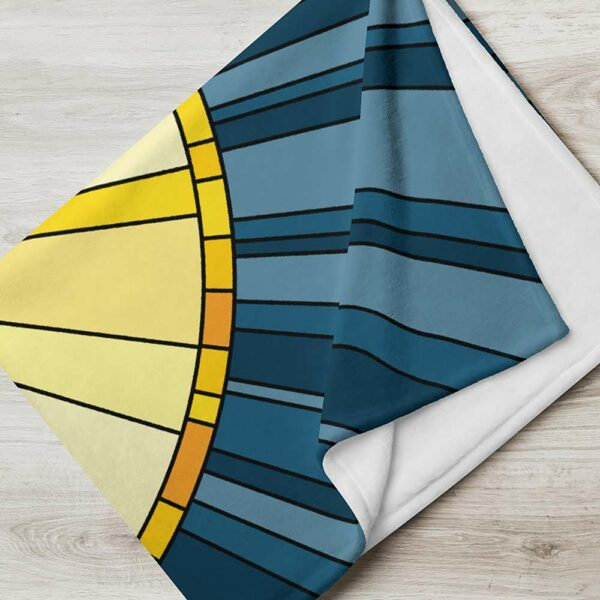 folded blanket with a large yellow sun on a dark blue background