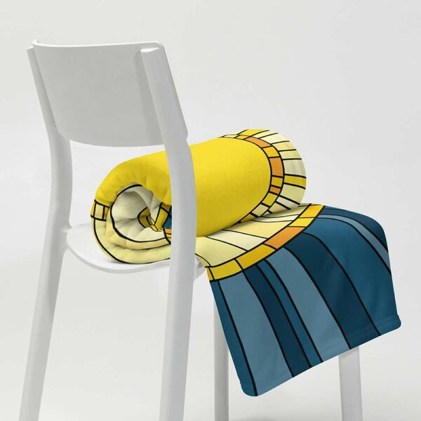 blanket with a large yellow sun on a dark blue background, rolled up on a chair