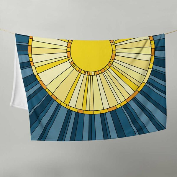 blanket with a large yellow sun on a dark blue background, hanging on a clothes line
