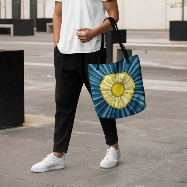 person holding a tote bag with black handles and a yellow sun design on a blue background
