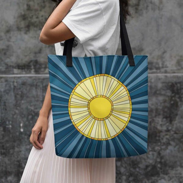 woman holding a tote bag with black handles and a yellow sun design on a blue background