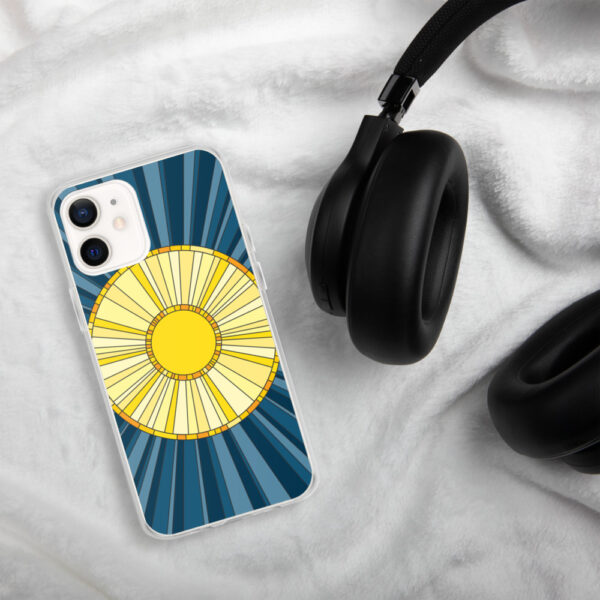 iphone case with a geometric design of a yellow sun on a blue background sitting next to headphones