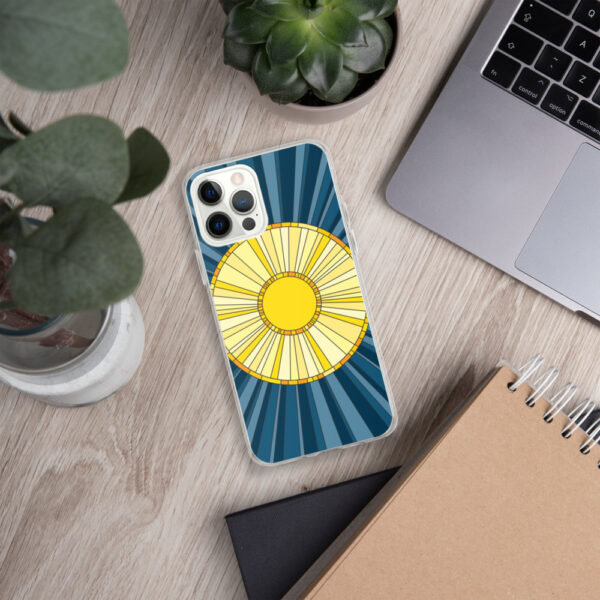 iphone case with a geometric design of a yellow sun on a blue background sitting next to a laptop