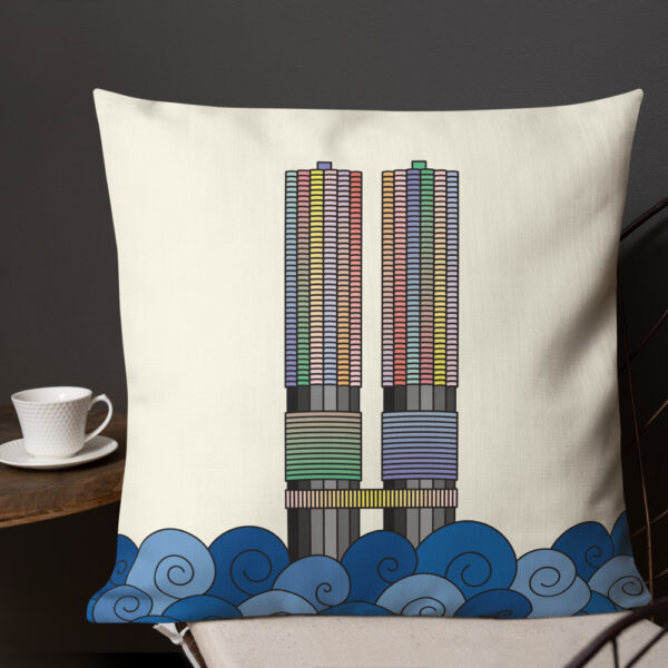 square pillow with a colorful illustration of the two marina city towers in chicago with a yellow background sitting on a chair