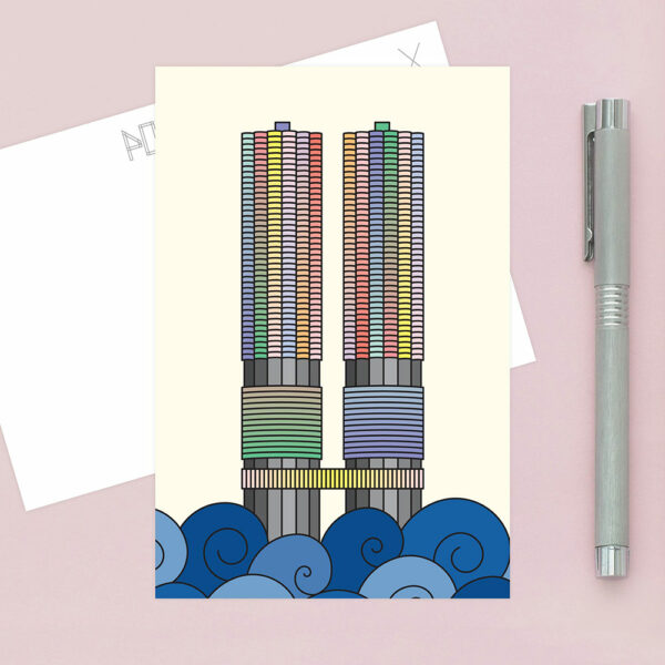postcard with a colorful illustration of the two marina city towers in chicago, sitting on a table
