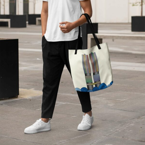 person holding a yellow tote bag with black handles and a colorful illustration of the two marina city towers in chicago