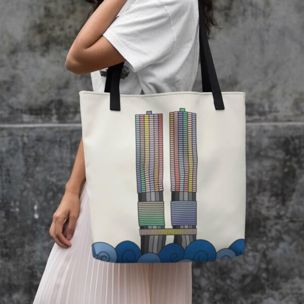woman holding a yellow tote bag with black handles and a colorful illustration of the two marina city towers in chicago