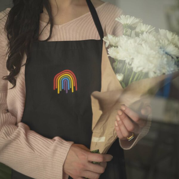 woman holding flowers and wearing a black apron with an embroidered dripping rainbow design in the center