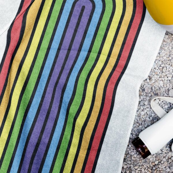 white beach towel with a colorful dripping rainbow design next to a water bottle