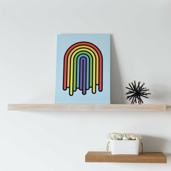 vertical stretched canvas print with a colorful dripping rainbow design sitting on a shelf