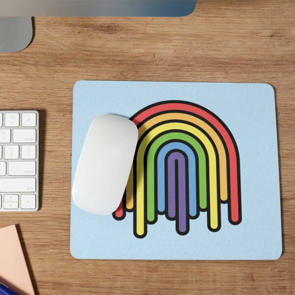 mouse pad with a colorful dripping rainbow design with a computer mouse and keyboard