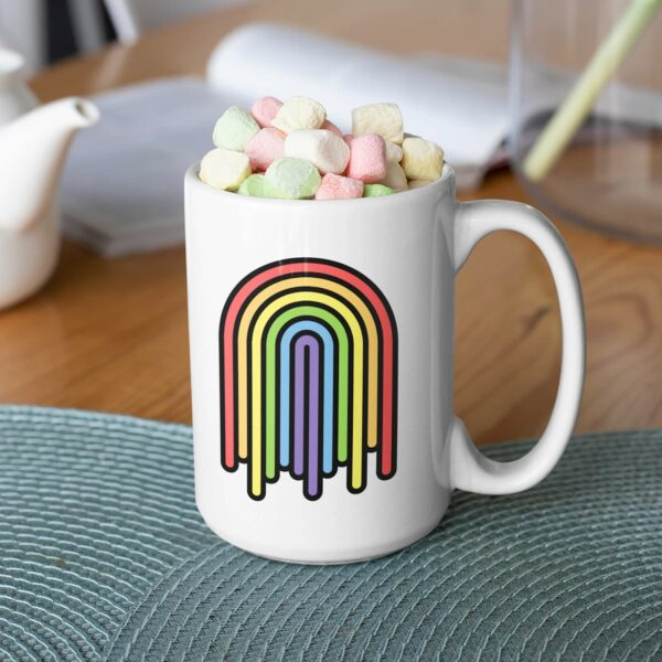 15 ounce white ceramic coffee mug with a colorful dripping rainbow on the side filled with marshmallows