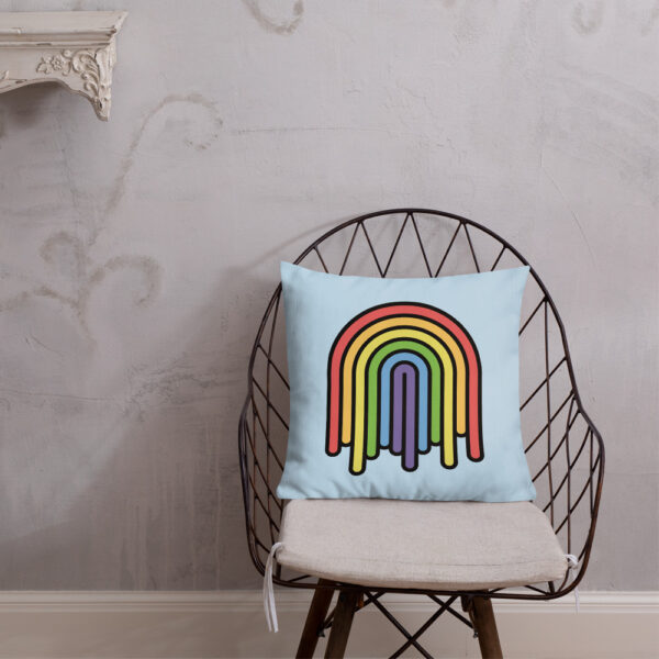 square pillow with a colorful dripping rainbow design on a light blue background sitting on a chair