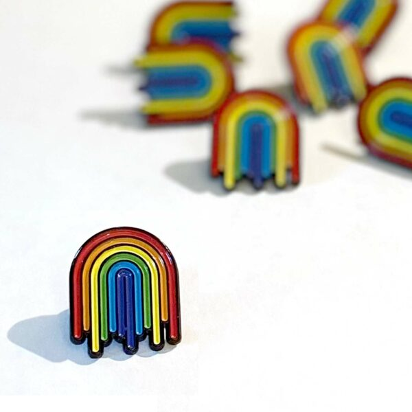 group of colorful dripping rainbow enamel pins