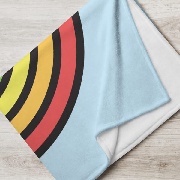 folded blanket with a large colorful dripping rainbow on a light blue background