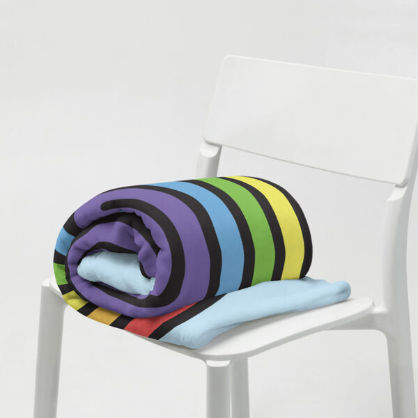 blanket with a large colorful dripping rainbow on a light blue background, rolled up on a chair