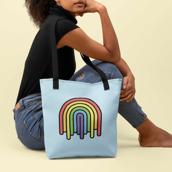 woman sitting next to a light blue tote bag with black handles and a colorful dripping rainbow design