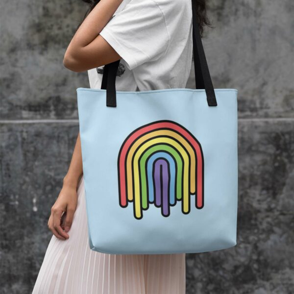 woman holding a light blue tote bag with black handles and a colorful dripping rainbow design