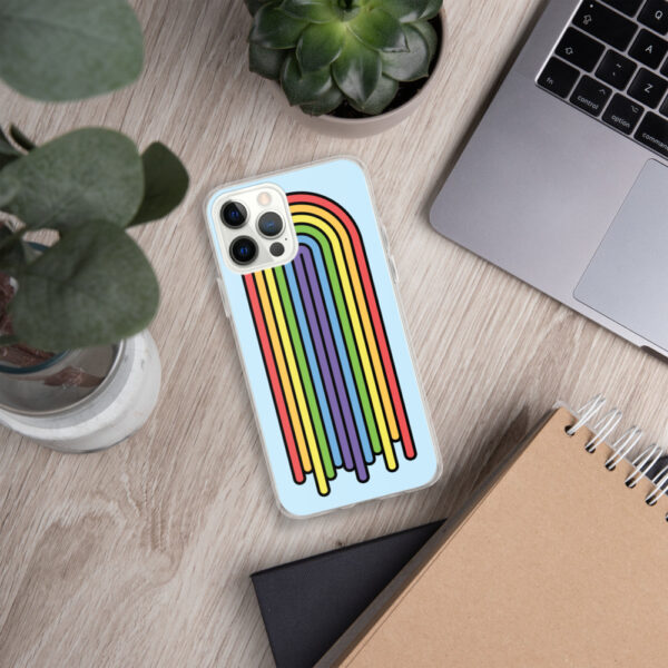 iphone case with a colorful dripping rainbow design on a light blue background sitting next to a laptop