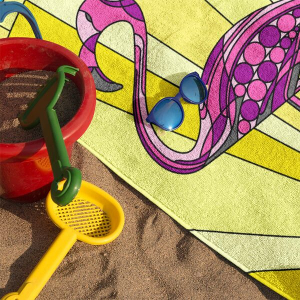 beach towel with a colorful pink flamingo standing in water in front of a sun - on sand with sunglasses