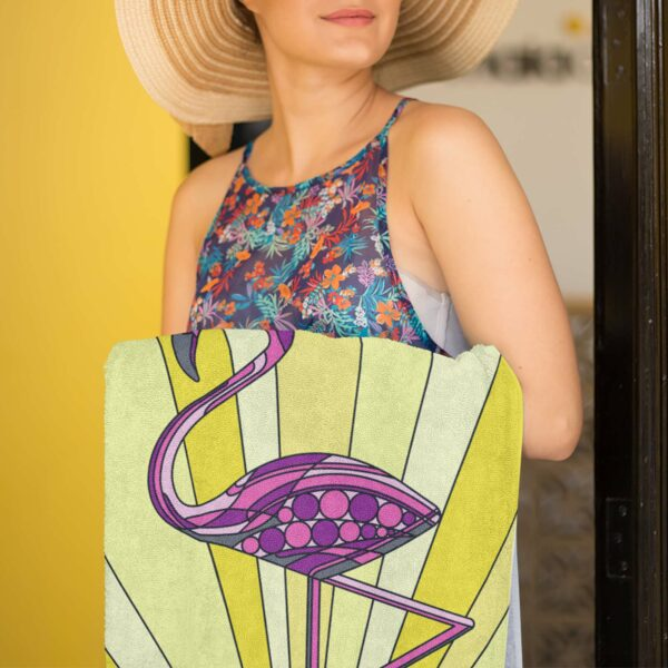 woman holding a beach towel with a colorful pink flamingo standing in water in front of a sun