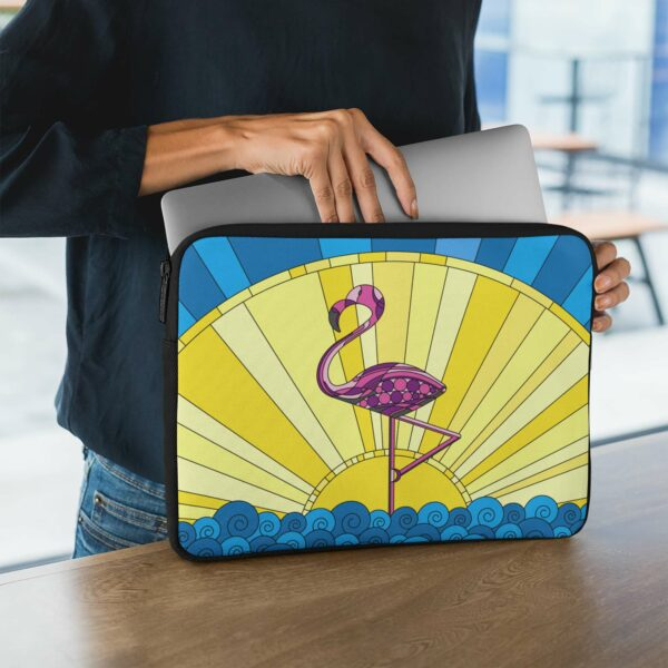 person holding a laptop sleeve with a tropical design of a pink flamingo standing in water in front of a sun