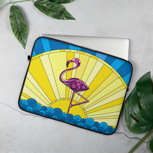 laptop sleeve with a tropical design of a pink flamingo standing in water in front of a sun - sleeve is sitting on a table