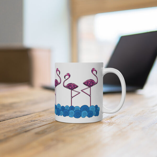 11 ounce white ceramic coffee mug with a design of pink flamingos standing in water wrapped around the sides sitting on a table