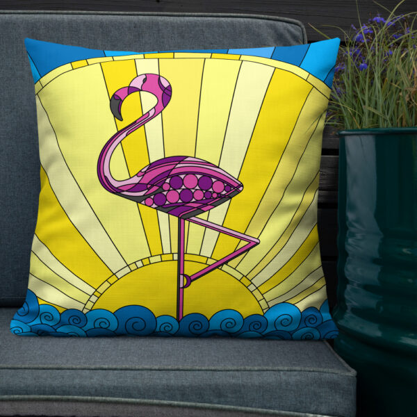 square pillow with a pink flamingo standing in waves in front of a yellow sun design sitting on a chair next to a plant