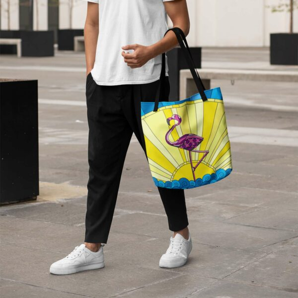 person holding a tote bag with black handles and a colorful design of a pink flamingo standing in water in front of a yellow sun