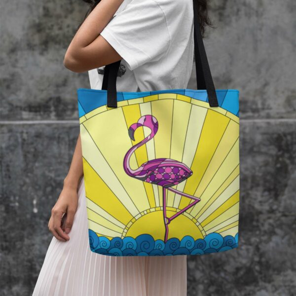 woman holding a tote bag with black handles and a colorful design of a pink flamingo standing in water in front of a yellow sun