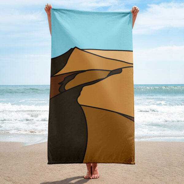 person on a beach holding a beach towel with a brown desert sand dune design