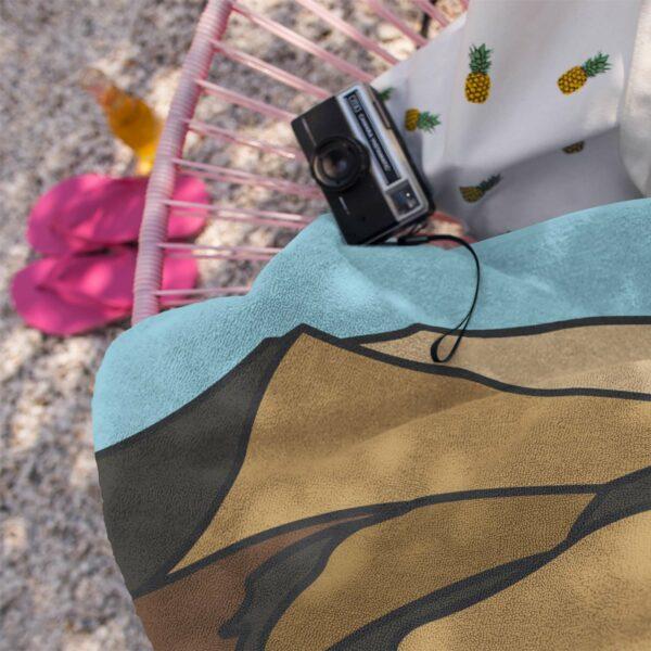 beach towel with a brown desert sand dune design next to a camera