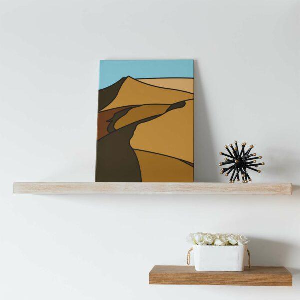 vertical stretched canvas print with a minimalist desert landscape design sitting on a shelf