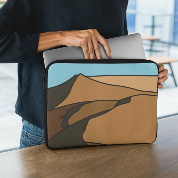 person holding a laptop sleeve with a minimalist desert landscape design