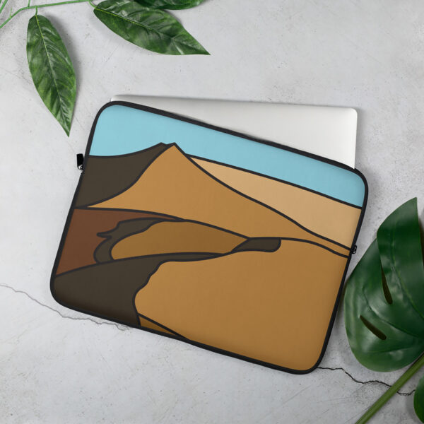 laptop sleeve with a minimalist desert landscape design sitting on a table