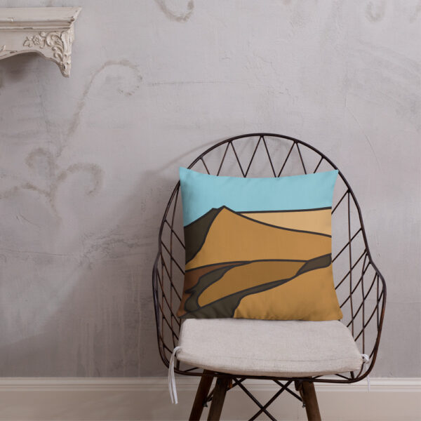 square pillow with a minimalist desert sand dune landscape design sitting on a chair